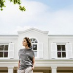 Woman in front of large home