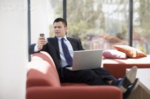 Businessman with laptop on sofa