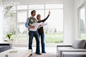 Couple holding building plans and discussing remodel