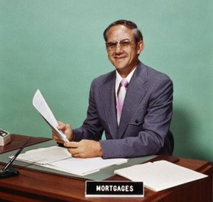 Man at desk holding papers with mortgage officer sign