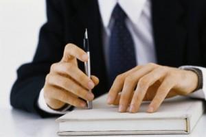 Businessman's hands on book, holding pen