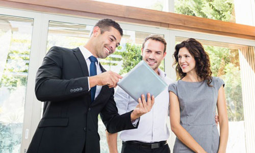 A real estate agent shows two clients listing information on a tablet.