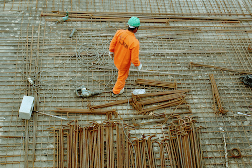 A construction worker in a green hardhat and an orange jumpsuit on the worksite.