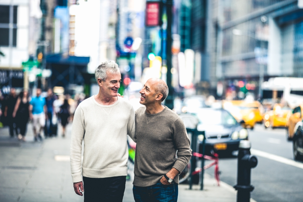 Gay couple walking in New York downtown. They are happy visiting the popular spots of the city.