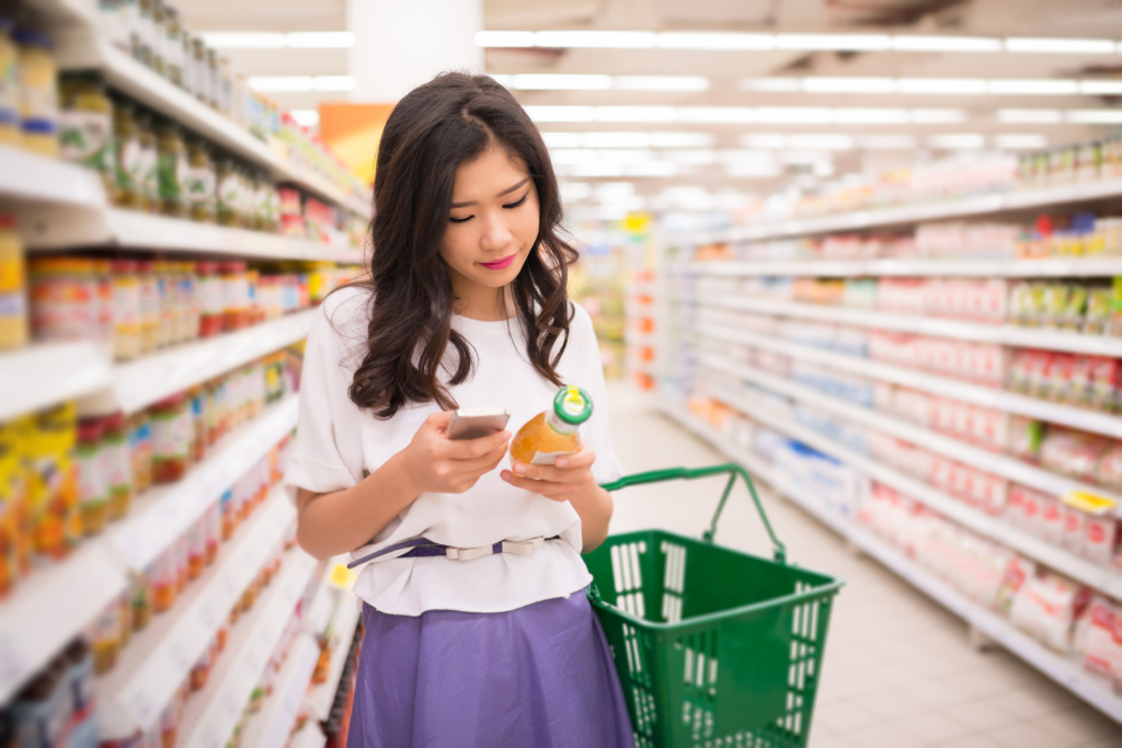 Young woman reading information about the product on the phone